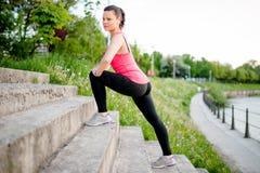 Vrouwelijke atleet die en zich langs een rivier bij schemer uitrekken lopen Royalty-vrije Stock Fotografie