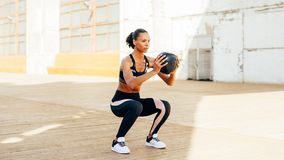 Vrouwelijke atleet die hurkende oefeningen doen stock afbeeldingen