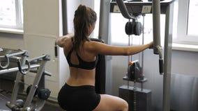 Vrouwelijke atleet die omgekeerd pec-Dek flye in gymnastiek binnen doen stock footage