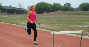 Vrouwelijke atleet die over hindernis op rasspoor 4k springen stock videobeelden