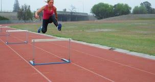 Vrouwelijke atleet die over hindernis op rasspoor 4k springen stock footage