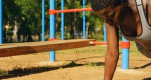 Vrouwelijke atleet die plank in het park 4k doen stock videobeelden