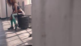 Vrouwelijke atleet die rust na het uitoefenen nemen bij gymnastiek stock videobeelden