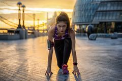 Vrouwelijke atleet klaar om haar vroege ochtendtraining in de stad te doen stock fotografie