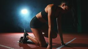 Vrouwelijke atleet op een donkere achtergrond om de sprint van het dwarsstootkussen van het land op de tredmolen op een donkere a stock videobeelden