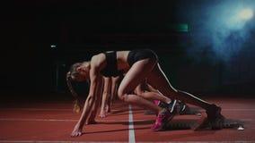 Vrouwelijke atleten die bij renbaan vóór een ras opwarmen in langzame motie stock video