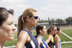 Vrouwelijke Atleten die zich in Lijn op Gebied bevinden Royalty-vrije Stock Foto