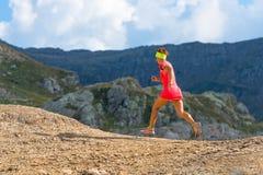 Vrouwelijke atletenlooppas in de bergen Stock Foto's