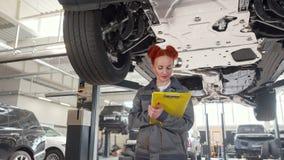 Vrouwelijke autowerktuigkundige die onder auto op een lift, het schrijven nota's op klembord lopen stock videobeelden