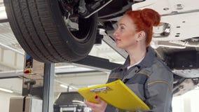 Vrouwelijke autowerktuigkundige die wielen die van een auto op een lift onderzoeken, nota's over klembord nemen stock videobeelden