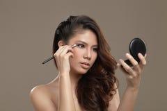 Vrouwelijke Aziaat die oogschaduw toepassen Stock Foto
