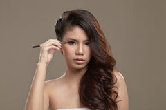 Vrouwelijke Aziaat die oogschaduw toepassen Royalty-vrije Stock Afbeelding