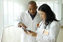 Vrouwelijke Aziatische arts die met Afrikaanse Amerikaanse arts met tablet spreken royalty-vrije stock afbeeldingen