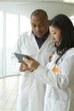 Vrouwelijke Aziatische arts die met Afrikaanse Amerikaanse arts met tablet spreken stock afbeeldingen
