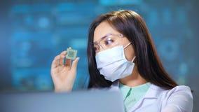 Vrouwelijke Aziatische ingenieur die met microchip bij modern elektronisch productielaboratorium werken die computer met behulp v stock videobeelden