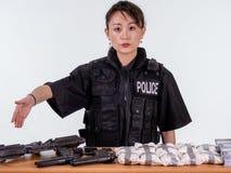 Vrouwelijke Aziatische politieman die gegrepen goederen tonen stock afbeelding