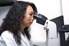 Vrouwelijke Aziatische wetenschapper die ooglenzen van microscoop onderzoeken Royalty-vrije Stock Fotografie