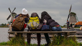 Vrouwelijke Backpackers voor traditionele Nederlandse windmolens Royalty-vrije Stock Afbeelding