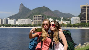 Vrouwelijke backpackerstoeristen met smartphone in Rio de Janeiro met Christus de Verlosser op achtergrond. Stock Foto's
