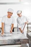 Vrouwelijke Baker Cleaning Table While Medewerker die Zwabber in Bakkerij gebruiken stock foto