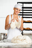 Vrouwelijke Baker Holding Dough At Lijst stock afbeelding
