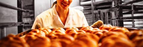 Vrouwelijke bakker die in bakkerij werken stock foto's