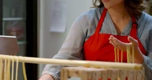 Vrouwelijke bakker die deegwaren op deegwarenrek 4k schikken stock footage