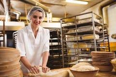 Vrouwelijke bakker die een deeg kneden stock afbeelding
