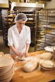 Vrouwelijke bakker die een deeg kneden royalty-vrije stock afbeelding
