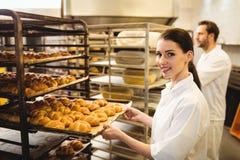 Vrouwelijke bakker die een dienblad van michetta houden royalty-vrije stock afbeelding