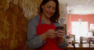 Vrouwelijke bakker die mobiele telefoon in bakkerijwinkel 4k met behulp van stock video