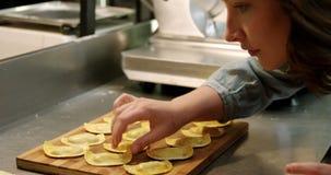Vrouwelijke bakker die raviolideegwaren in bakkerijwinkel 4k schikken stock footage