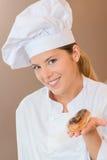 Vrouwelijke bakker die u voorstellen met eclair stock afbeelding