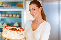 Vrouwelijke bakker of gebakjechef-kok met torte stock fotografie
