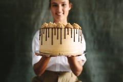 Vrouwelijke bakker met een heerlijke cake stock foto