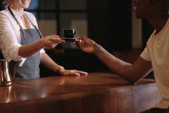 Vrouwelijke barista dienende klant binnen een koffiewinkel royalty-vrije stock afbeeldingen