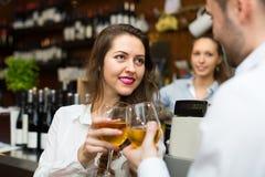 Vrouwelijke barista en twee cliënten Stock Afbeeldingen