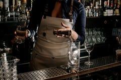 Vrouwelijke barman die een alcoholische drank toevoegen in het glas met I royalty-vrije stock foto