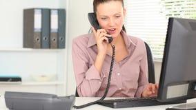Vrouwelijke beambte die de telefoon beantwoorden stock footage
