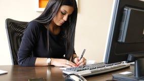 Vrouwelijke beambte die en controle schrijven ondertekenen stock fotografie