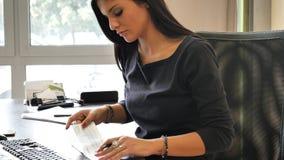 Vrouwelijke beambte die en controle schrijven ondertekenen stock foto