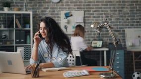 Vrouwelijke bedrijfseigenaar die op mobiele telefoon in bureau spreken die gebruikend laptop opdracht geven tot stock video