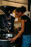 Vrouwelijke bedrijfseigenaar die zich bij de roosterende machine van de koffieboon bevinden royalty-vrije stock afbeelding
