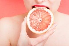 Vrouwelijke beet een plak van grapefruit stock afbeelding