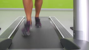 Vrouwelijke benen die en op tredmolen in gymnastiek aanstoten lopen Jonge vrouw die tijdens cardiotraining uitoefenen Voeten meis stock video