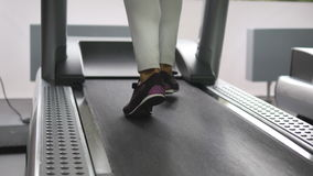 Vrouwelijke benen die en op tredmolen in gymnastiek lopen lopen Jonge vrouw die tijdens cardiotraining uitoefenen Voeten meisjes  stock footage
