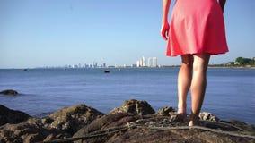 Vrouwelijke benen die op de rotsen door het overzees op een zonnige dag lopen stock footage