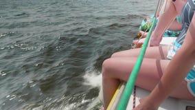 Vrouwelijke benen die over kant van wit varend jacht hangen stock footage
