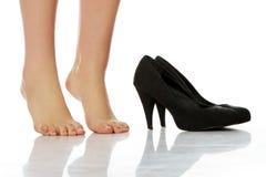 Vrouwelijke benen die zich op tenen naast hoge hielen bevinden Stock Fotografie