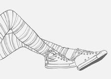 Vrouwelijke benen in gestreepte kousen en tennisschoenen Stock Afbeeldingen